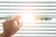 Ciechi di finestra di apertura del giovane, primo piano immagini stock