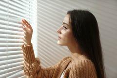 Ciechi di finestra di apertura della giovane donna immagine stock libera da diritti