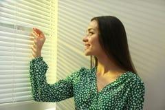 Ciechi di finestra di apertura della giovane donna fotografia stock libera da diritti