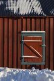 Ciechi di finestra chiusi della cabina di legno rossa in neve, textu a forma di z fotografia stock libera da diritti