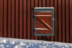 Ciechi di finestra chiusi della cabina di legno rossa in neve, textu a forma di z fotografie stock libere da diritti