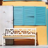 Ciechi di un banco, della porta aperta e del blu fotografia stock
