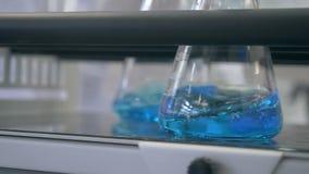 Ciecz miesza w laboranckim glassware mieszać błękitnego ciecz w laboranckim glassware mieszać w laboranckiej kolbie zdjęcie wideo