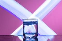 Ciecz z lodem w szkle na odbijającej powierzchni na czerwonawym tle obraz royalty free