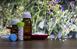 Ciecza i globula w górę wizerunku homeopatyczne pigułki w czerwonej łyżce i butelce substancja z rozciągniętymi białego cukieru p zdjęcia royalty free