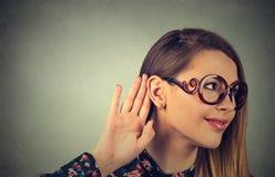 Ciekawa śmieszna przyglądająca kobieta trzyma jej rękę blisko ucho i słucha zdjęcie royalty free