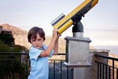 Ciekawa chłopiec, patrzeje przez teleskopu przy coś interestin Obraz Stock