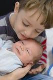Ciekawa chłopiec trzyma jego młodszego brata Fotografia Royalty Free