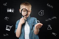 Ciekawa chłopiec trzyma powiększać, szklany przez go patrzeć - i fotografia royalty free