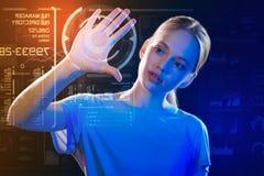 Ciekawa dziewczyna dotyka ekran i skanuje jej rękę obraz stock