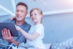 Ciekawa dziewczyna używa laptop z jej ojcem Zdjęcie Royalty Free