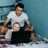 Ciekawa dziewczynka używa laptop siedzi w domu łóżko zdjęcie stock