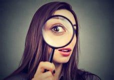 Ciekawa kobieta patrzeje przez powiększać - szkło obraz stock