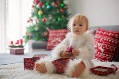 Ciekawa mała berbeć chłopiec, ubierająca w handknitted białym kombinezonie, kłama na leżance bawić się z prezentami obrazy stock