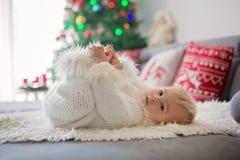 Ciekawa mała berbeć chłopiec, ubierająca w handknitted białym kombinezonie, kłama na leżance bawić się z prezentami obraz stock