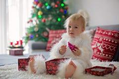 Ciekawa mała berbeć chłopiec, ubierająca w handknitted białym kombinezonie, kłama na leżance bawić się z prezentami obraz royalty free