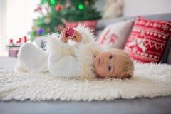 Ciekawa mała berbeć chłopiec, ubierająca w handknitted białym kombinezonie, kłama na leżance bawić się z prezentami zdjęcia royalty free