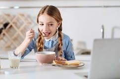Ciekawa mała dziewczynka ogląda wideo podczas gdy mieć śniadanie Obraz Stock
