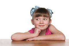 Ciekawa mała dziewczynka przy biurkiem zdjęcie stock