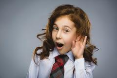 Ciekawa uśmiechnięta dziewczyna słucha Zbliżenie portreta dziecka przesłuchanie coś, rodzice opowiada, wręcza uszaty gest odizolo zdjęcie stock