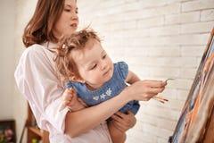 Ciekawi małej dziewczynki dopatrywania matki farby obrazki obraz royalty free