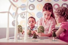 Ciekawi mali naukowowie siedzi w klasowej i rekonesansowej alternatywnej energii obrazy royalty free