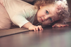Ciekawy śliczny dziecko chuje pod łóżkiem w dzieciaka pokoju i patrzeje okaleczający zdjęcia stock