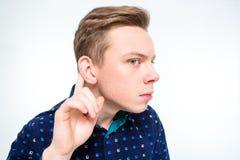 Ciekawy blond młody człowiek próbuje słuchać plotki fotografia stock