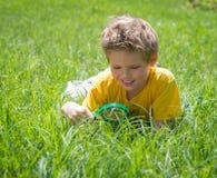 Ciekawy dzieciak na łąkowym patrzejący trawy z powiększać - szkło Śliczna chłopiec robi eksperymentom outdoors fotografia royalty free