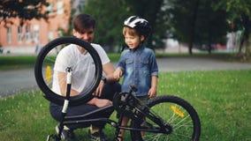 Ciekawy dziecko jest ubranym hełm jest przędzalnianym rowerowym kołem i pedałuje podczas gdy jego ojciec opowiada on na gazonie w zbiory
