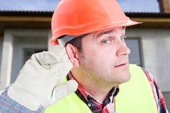 Ciekawy inżynier lub budowniczy słucha wiadomość obrazy royalty free