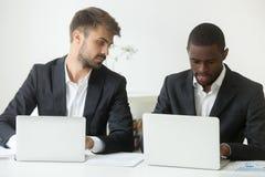 Ciekawy Kaukaski pracownik patrzeje amerykanina afrykańskiego pochodzenia kolegi w zdjęcia stock
