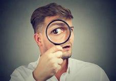 Ciekawy mężczyzna patrzeje przez magnifier zdjęcie stock