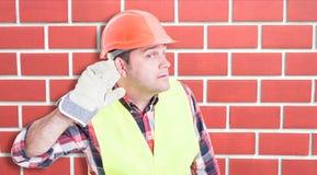 Ciekawy męski budowniczy słucha wiadomość Zdjęcie Stock