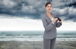 Ciekawy młody bizneswoman pozuje z lornetkami Zdjęcie Royalty Free