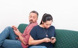 Ciekawy męski patrzeje kobieta telefon Obrazy Stock