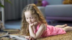 Ciekawy ma?ej dziewczynki lying on the beach na pod?oga, czyta ciekawego children storybook zdjęcie royalty free