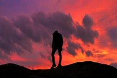 Ciekawy szczeg?? Sylwetka młody facet wspina się jego cel Bardzo ładny zmierzch i czerwieni niebo w tle obrazy royalty free