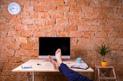 Cieki biznesmen, siedzi przy biurowym biurkiem, ściana z cegieł Zdjęcie Royalty Free