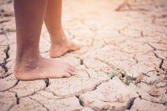 Cieki chłopiec na krakingowym suszą ziemię Zdjęcie Royalty Free