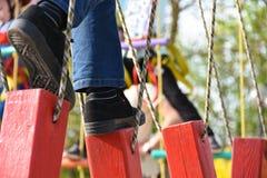 Cieki dziecko krok na obwieszeniu notują dalej przeszkoda kurs w parku rozrywki, plenerowe aktywność, rockowy pięcie, niebezpiecz obraz stock