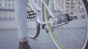 Cieki którego w górę jedzie je w mieście zamkniętym i siedzi na bicyklu młody człowiek Miastowy pejzaż miejski w tle leisure zbiory wideo