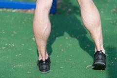 Cieki w czarnych sport mody butach na zielonej trawie Mięśniowe nogi z żyłami przy stadium lub areną na pogodny plenerowym Zdrowi zdjęcie stock