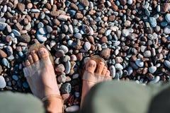 Cieki w sandałach przy otoczak plażą obraz stock