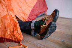 Cieki w włóczkowych skarpetach Mężczyzna jest relaksującym pobliskim namiotem i rozgrzewkowy up jego cieki w włóczkowych skarpeta Zdjęcia Stock