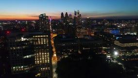 Ciel égalisant orange chaud de coucher du soleil au-dessus du paysage urbain lumineux d'illumination de lumière de nuit de ville  banque de vidéos