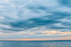 Ciel au-dessus des eaux calmes de baie au coucher du soleil photos stock