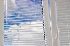 Ciel avec des nuages à travers les abat-jour vénitiens sur la fenêtre Photo libre de droits