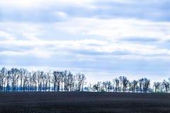 Ciel avec des nuages au-dessus des champs noirs Image libre de droits
