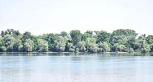 Ciel bleu, arbres verts, rivière bleue Images stock
